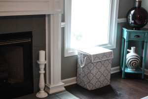 Painted fireplace with laundry basket that provides storage for toys.