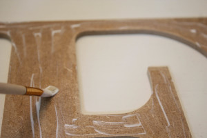 How to make a modge podge letter. Putting modge podge onto the wooden letter.