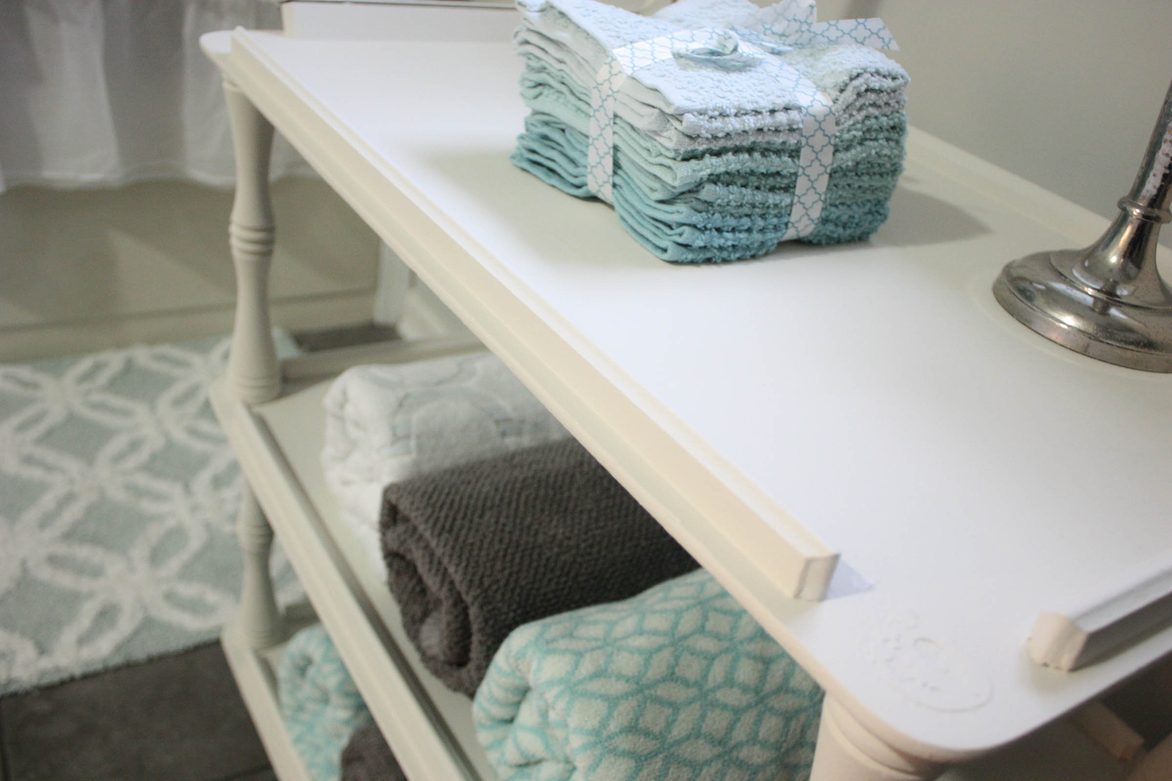 chalk painted vintage tea cart holding towels and rags
