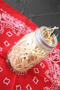 Barnyard birthday party. Mason jar filled with raffia.