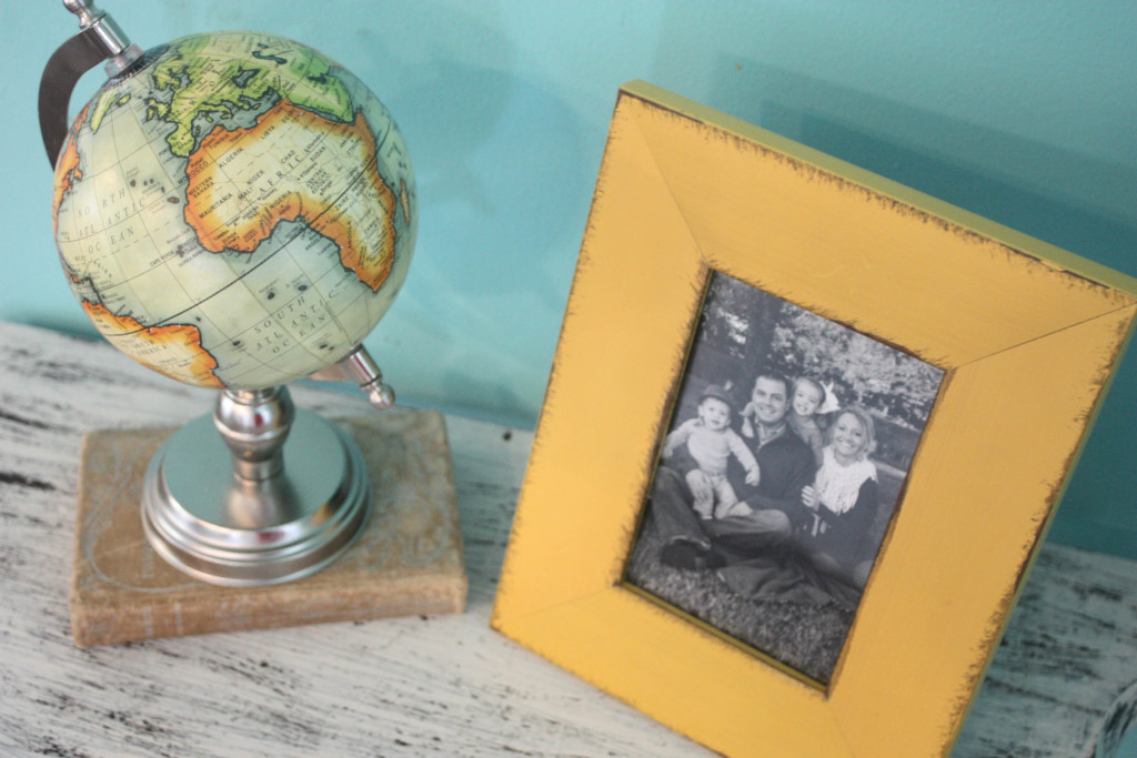 Old book, frame and globe on distressed half table