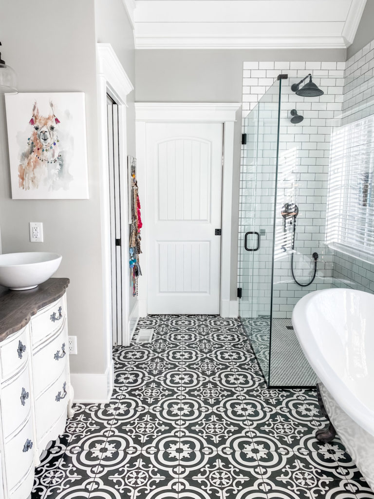 full view of master bathroom and black and white flooring