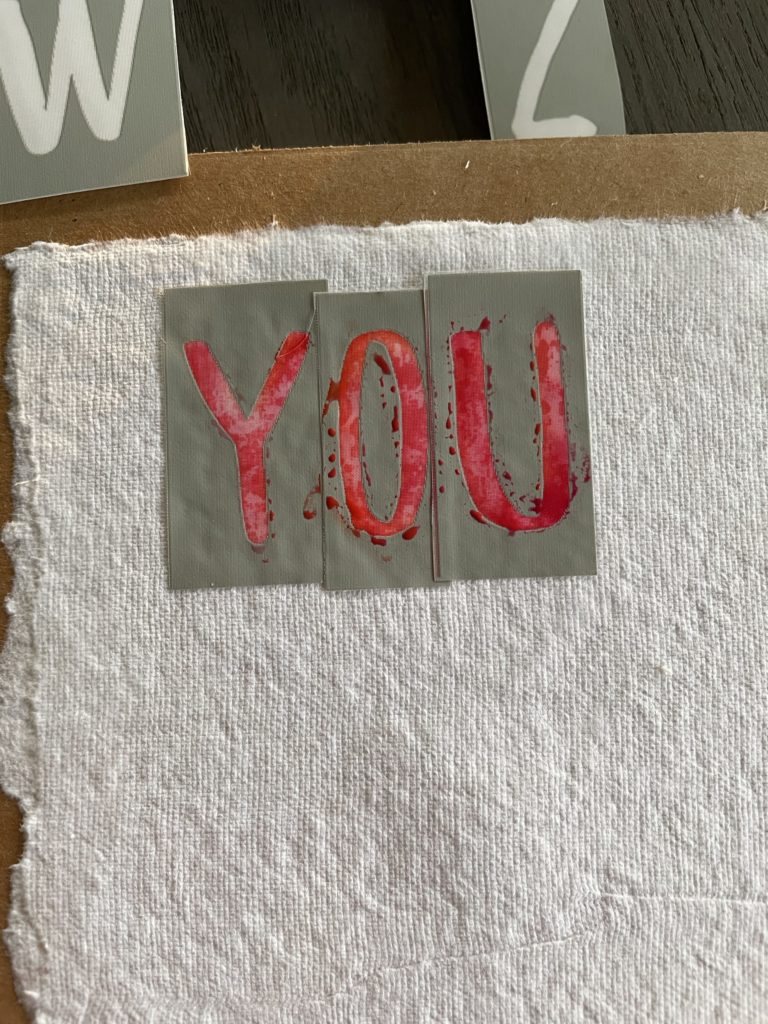 stenciling the paint onto the watercolor paper