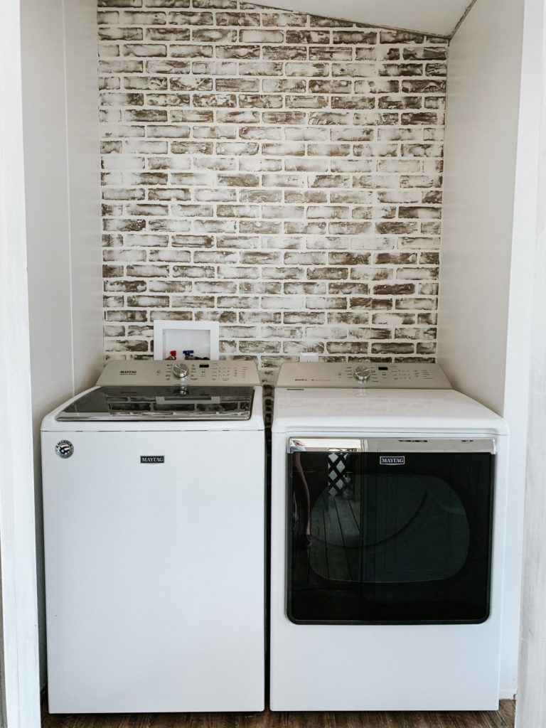 laundry room in a mobile home in process of installing brick board to german smear