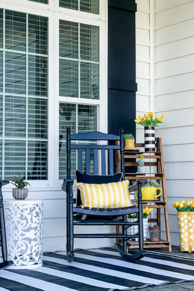 rocking chairs with yellow decor on modern spring front porch