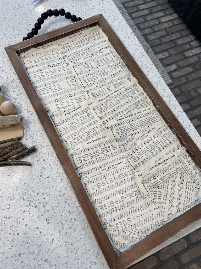 place and mod podge hymnal paper on sign