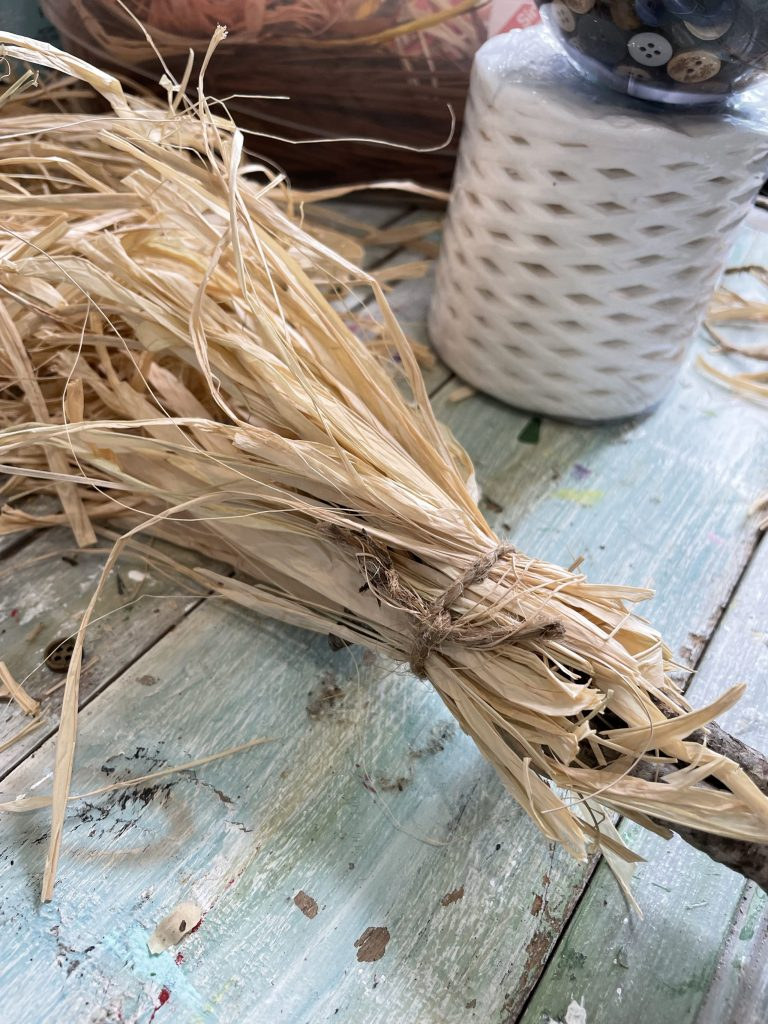 take the other side of the sticks, and wrap them with raffia to create the broom