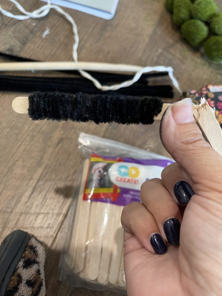 wrap pipe cleaners around the popsicle stick legs