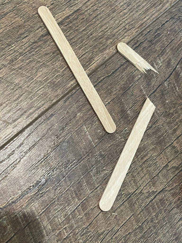 break popsicle sticks to shape of spider legs