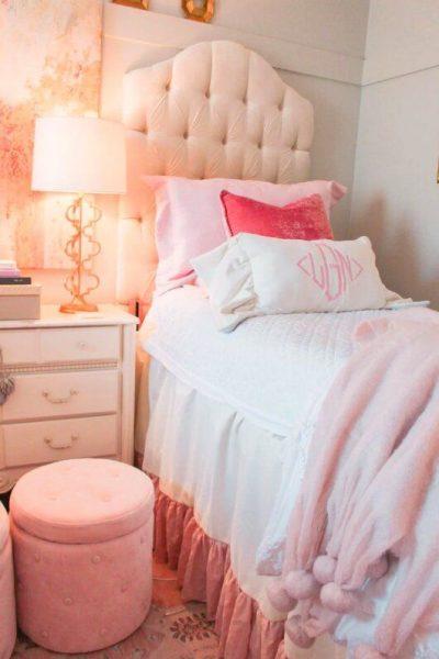 dorm room with headboard and ottoman