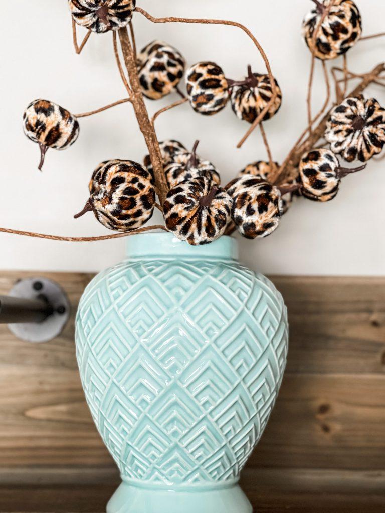 blue vase filled with leopard pumpkins