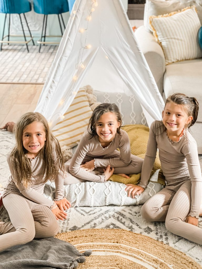 girls in their matching pajamas in the teepee