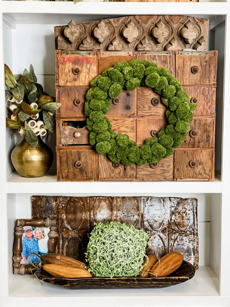 built in shelving styled with natural elements including green moss wreath, moss ball, dough bowl, antique drawer set, and rusted metal