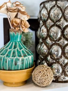 large metallic vase styled with aqua vase and wooden roses