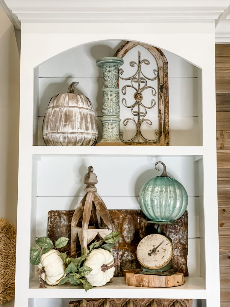 built in shelving styled with natural elements including wooden lanter, vintage scale, glass pumpkin, wooden pumpkin